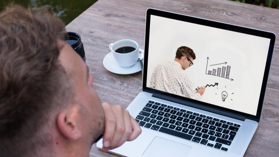 A man looking at a laptop screen that shows another man drawing on a whiteboard.